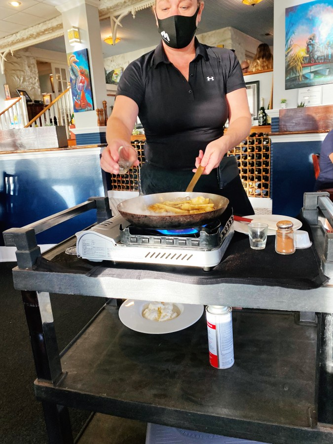 woman cooking on portable grill - bananas foster