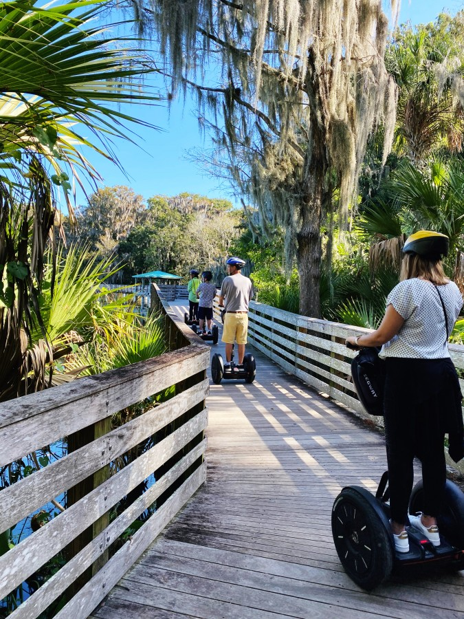 people on Segway on wooden boardwalk with trees